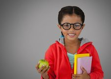 Girl against grey background with apple and books and glasses. Digital composite of Girl against grey background with apple and books and glasses Royalty Free Stock Photos