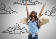 Girl against grey background with cardboard pilot wings and cloud illustrations Royalty Free Stock Photos