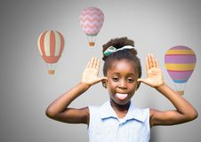 Girl against grey background making funny face sticking out tongue and hot air balloons Royalty Free Stock Photos