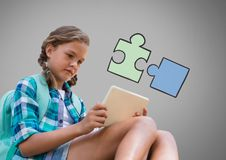 Girl against grey background with tablet device and jigsaw puzzle illustration. Digital composite of Girl against grey background with tablet device and jigsaw royalty free stock photos