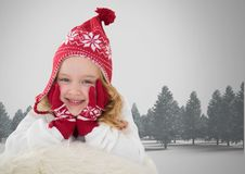 Girl against grey background with warm Christmas Winter hat and gloves and trees Stock Photography