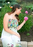 Girl against pink peony flowers Royalty Free Stock Photography