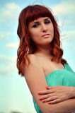 Girl against the sky. Red-haired girl on a background of blue sky Royalty Free Stock Photos
