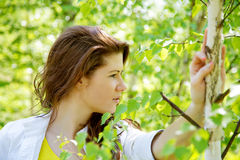 Girl against spring foliage Stock Photography