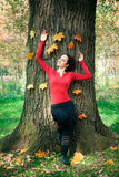 Girl against tree trunk Royalty Free Stock Image