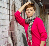 Girl against the wall. Girl against a wall wearing a scarf and a pink cardigan Royalty Free Stock Images