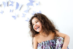 The girl against a wall decorated with butterfly Stock Photos