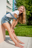 Girl against a wall and fooled laugh. She leaned against the wall and resting his knees laughing infectiously Royalty Free Stock Photography