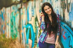 The girl against a wall with graffiti. The youth-style girl leaning against the wall of graffiti sprayed in an urban environment royalty free stock photography