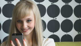 Girl aged 20s making selfie photo on smartphone. Young attractive model girl aged 20s making selfie photo on smartphone indoors stock footage