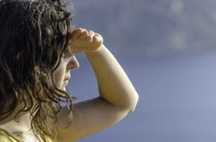 Girl ahead with the hand in forehead and the sea in the background. Stock Image