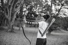 A girl aiming bow and arrow in the forest Royalty Free Stock Photography