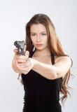 Girl aiming a gun Stock Images