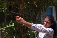 A girl aiming the gun. A teenage Indian girl aiming a gun carefully at distant target Stock Photography