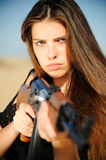 Girl aiming machine gun. Girl aiming a machine gun in the desert Stock Photography