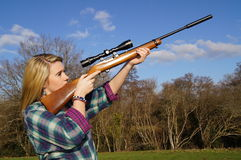 Girl Aiming Rifle. Girl with rifle shooting game in rural English countryside against blue sky Stock Images