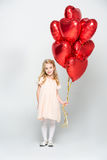 Girl with air balloons. Little girl holding bundle of red heart shaped air balloons on white Stock Images
