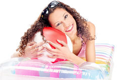 Girl on air mattress. Smiled curl girl with sun glasses in hair, laying air mattress and holding the ball, isolated on white Stock Image