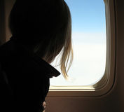Girl in airplane. Girl watching out on the sky that pass by Royalty Free Stock Photo