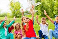 Girl with airplane toy and children sit behind. Girl with big white airplane toy and children sit behind her in the field during summer day Stock Photography