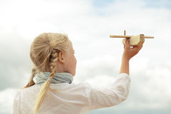 Girl and airplane toy on the cloudy sky Royalty Free Stock Images