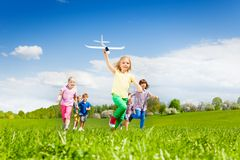 Girl with airplane toy runs fast and kids behind Stock Images