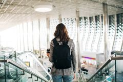 Girl at the airport from the back, holding coffee cup. royalty free stock photo