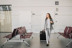 Girl at the airport, walking with her baggage. royalty free stock images