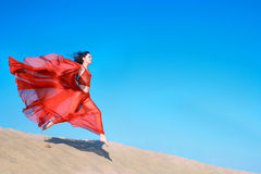 Girl in airy red dress running on sand dunes Stock Photos
