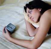 Girl and alarm clock Stock Images