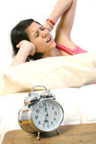 Girl and alarm clock. Girl covering her ears not wanting to wake up with the alarm. Isolated against a white background stock photo