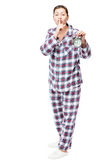 Girl with an alarm clock in checkered pajamas showing a gesture Stock Images
