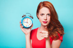 Girl with alarm clock. Redhead girl with alarm clock on blue background Stock Photos