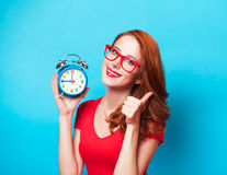 Girl with alarm clock. Redhead girl with alarm clock on blue background Stock Image