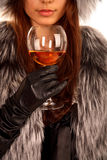 Girl with alcoholic beverage in a fur coat. The girl dressed in a fur coat keeps in a hand a glass with an alcoholic drink Stock Image
