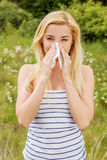 Girl with alergy blowing her nose. Stock Photo