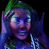 The girl aliens asleep. shrugs her shoulders. Ultraviolet make-up. She holds her hands near her face, next to her ears royalty free stock photo