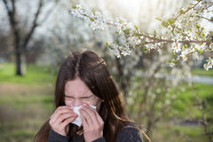 Girl with allergic reaction on blooming tree Stock Images