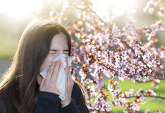 Girl with allergic reaction on blooming tree stock photo