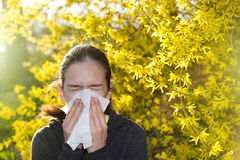 Girl with allergic reaction on blooming tree stock photography