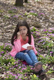Girl with allergic rhinitis sitting among primroses Royalty Free Stock Photos