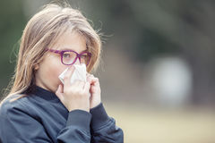 Girl with allergy symptom blowing nose. Teen girl using a tissue in a park Stock Photo