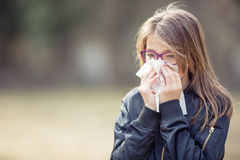 Girl with allergy symptom blowing nose. Teen girl using a tissue in a park Royalty Free Stock Photos