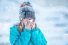 Girl with allergy symptom blowing nose. Teen girl using a tissue. In a winter park Stock Photos