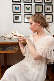 Girl with alligator skull. Girl in white vintage dress sitting in front of butterflies and holding a skull of an alligator stock photos