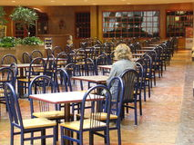 Girl alone. Girl sits alone at table royalty free stock photography