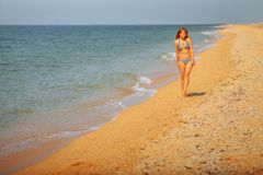 Girl alone in a bathing suit walking along the seashore royalty free stock photography