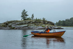 A girl alone in a boat. Sailing with oars in Lake Ladoga, Russia Stock Photography