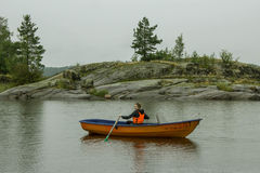 A girl alone in a boat. Sailing with oars in Lake Ladoga, Russia Royalty Free Stock Photography