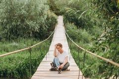 Girl alone emotions suspension bridge over gorge stock image